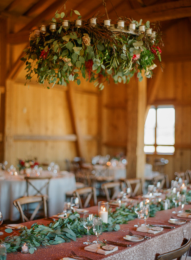 The gorgeous wedding chandeliers were with candles, lush greenery and blush blooms