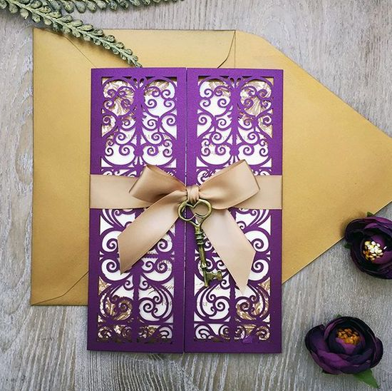a purple laser cut invitation with a vintage key attached and a gold envelope