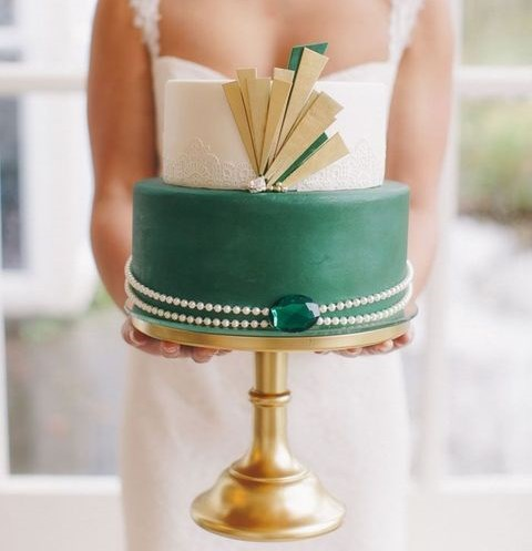 a round wedding cake with a white lace and an emerald lyaer with gold details, pearls and an emerald