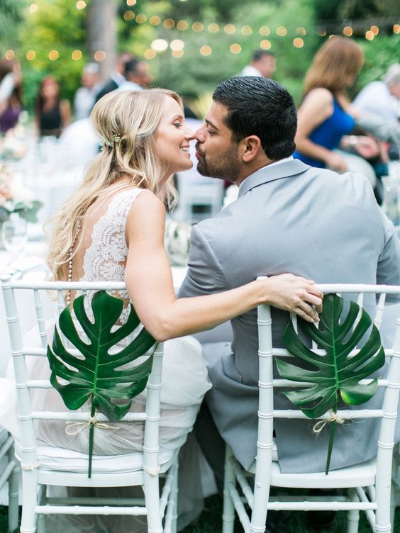 attach large tropical leaves to the couple's chairs to highlight them