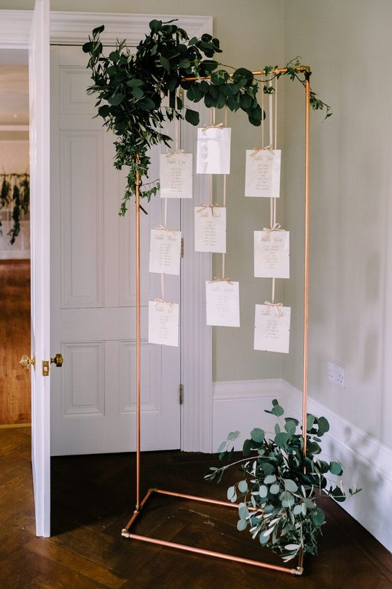 a copper frame with notes and eucalyptus as a unique seating chart