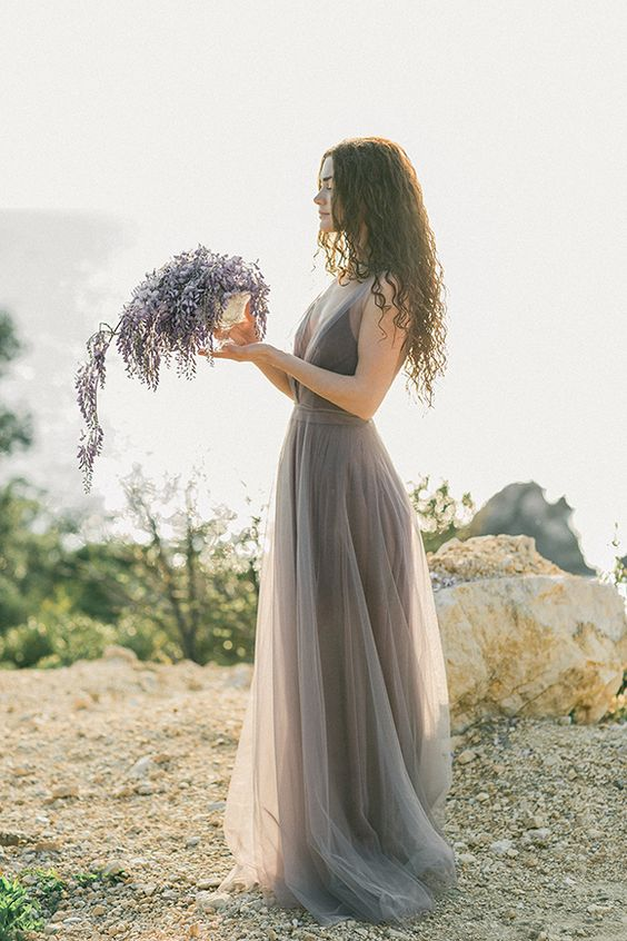 a grey lavender wedding dress with a plunging neckline and a lavender floral arrangement