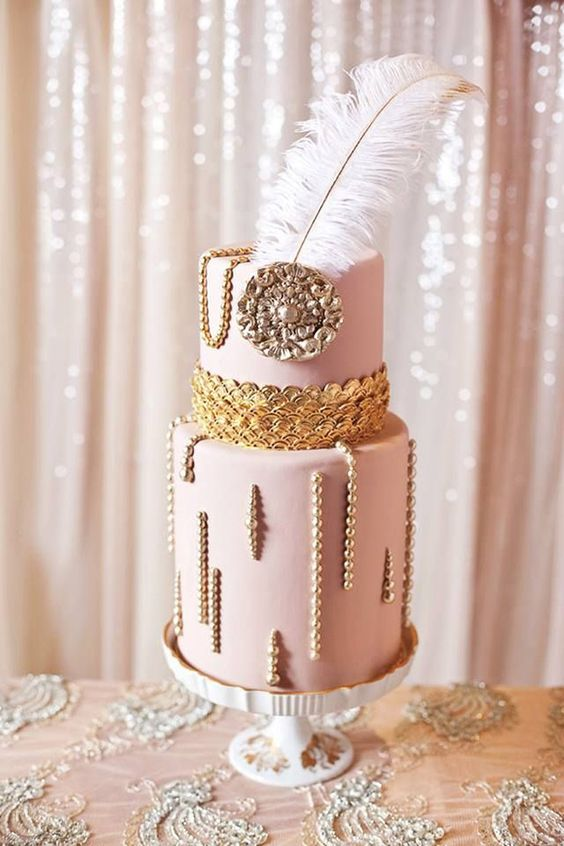 a pink wedding cake with pearls, gold scallops, a vintage brooch and a feather