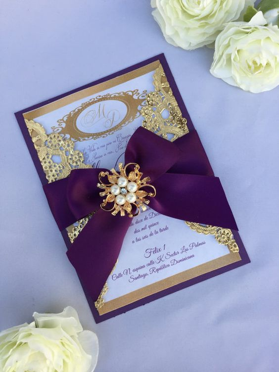 a refined laser cut wedding invitation with laser cut details and a pearl brooch on top
