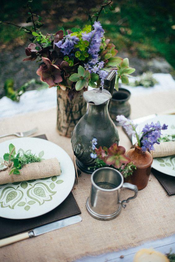 einen rustikalen Tisch, inspiriert von hobbits, mit grünen aptterned Platten, sackleinen, Leder und einfache Blüten