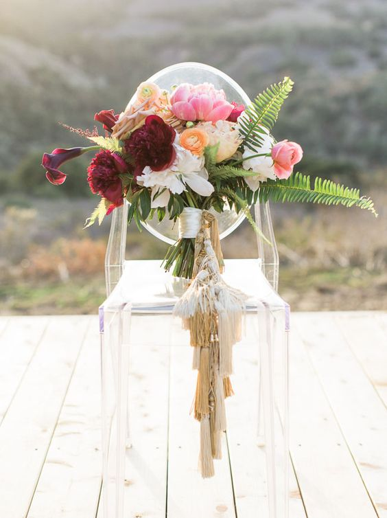 a cool and bold wedding bouquet with neutral tassels that decorated the wrap