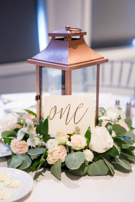 a copper lantern with lush blooms and a table number for a cool centerpiece