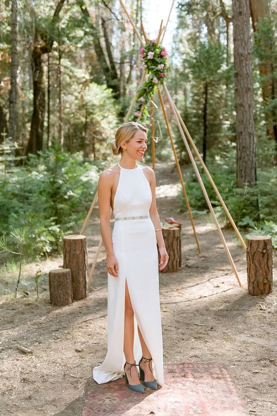 eine minimalistische neckholder-Ausschnitt Hochzeit Kleid mit einem verzierten Gürtel und dunkle grün suede Schuhe für eine Wald-Hochzeit