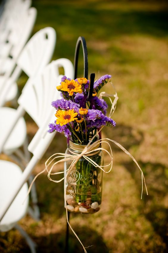 a rustic floral decoration with yellow and purple blooms and pebbles