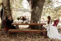 14 a rustic tablescape with burgundy velvet chairs right in the forest