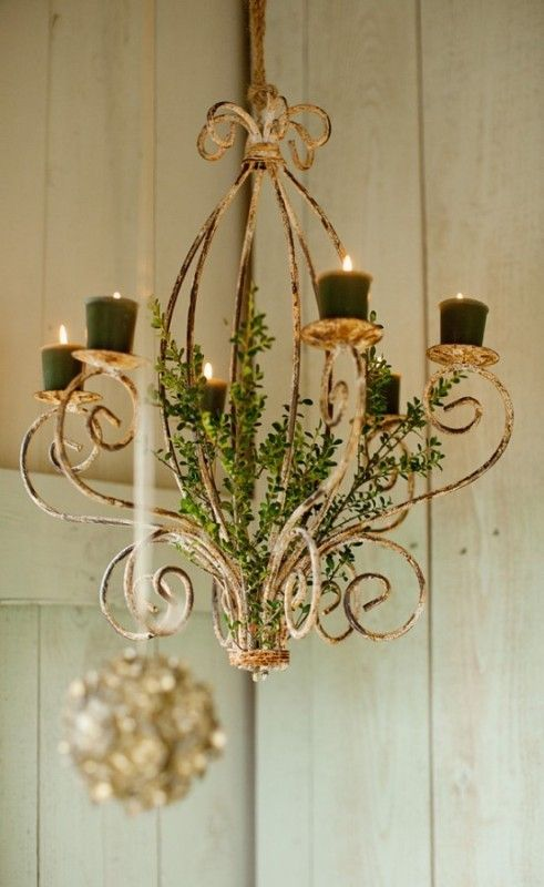Fancy a vintage chandelier decorated with greenery and with dark green candles