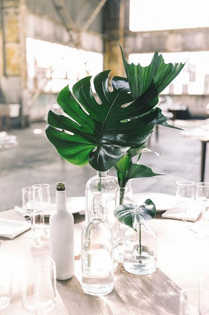 a wedding centerpiece with bottles and vases and tropical leaves for modern decor