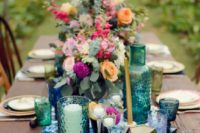 15 a boho tablescape with an indigo dyed table runner, emerald and indigo glasses and bold florals