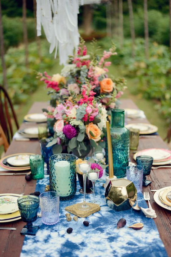 a boho tablescape with an indigo dyed table runner, emerald and indigo glasses and bold florals