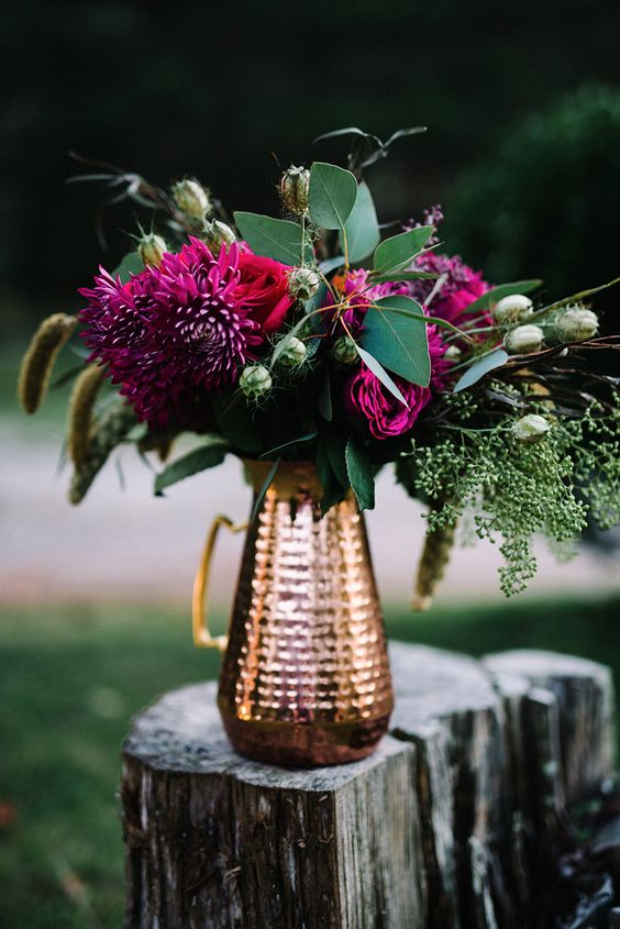 a copper pitcher with bold plum-colored blooms and lush grenenery for a centerpiece