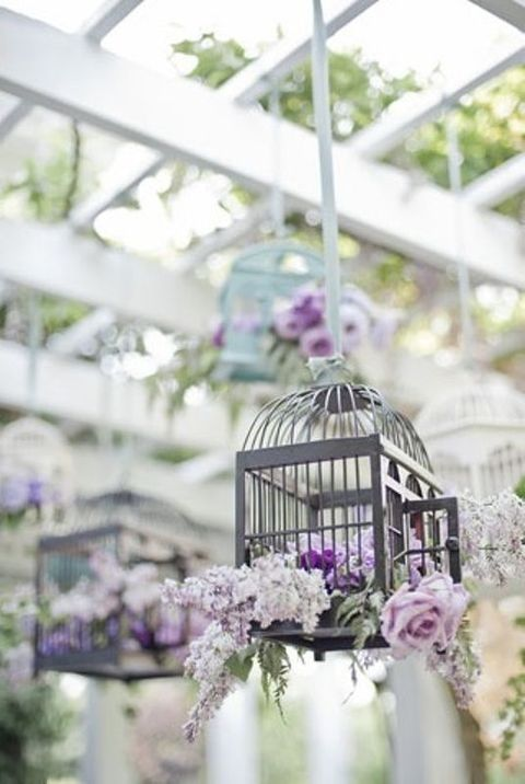 a lilac and lavender bloom arrangement in a suspended cage looks cool
