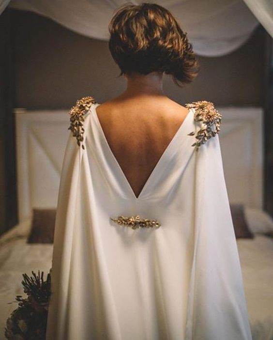 a plain white cape with statement gold jewelry on shoulders and back