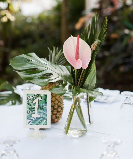 a tropical wedding centerpiece with a bold pink flower, a tiny pineapple skewer