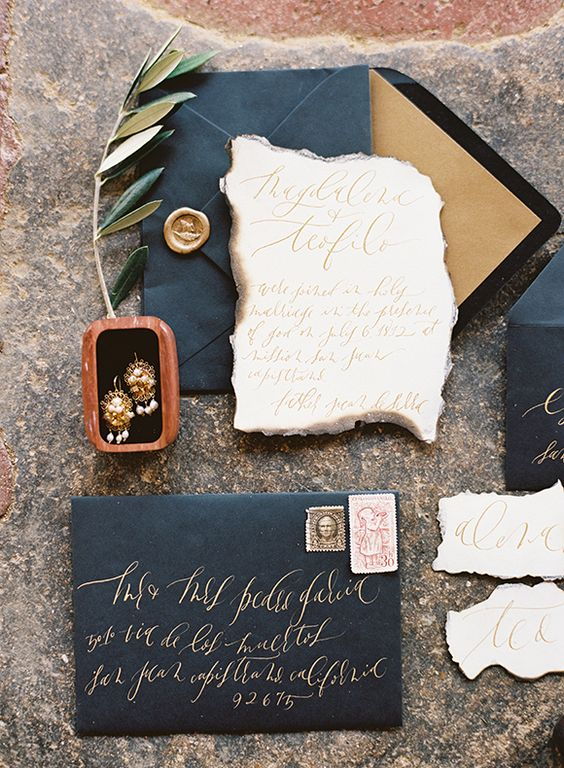 black wedding envelopes with gold calligraphy and neutral invites with a raw edge