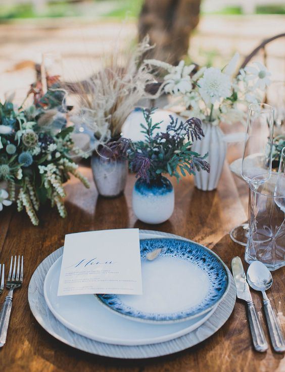 a coastal table setting accentuated with indigo vases and beautifully painted plates