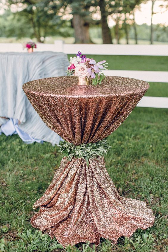 a copper sequin tablecloth for a wedding lounge, decorated with greenery and a small floral centerpiece