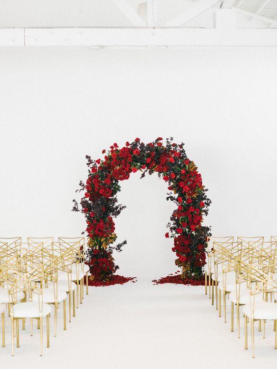 eine üppige rote rose und grün-Hochzeit-Bogen-mit gold und weißen Stühle bilden einen raffinierten Zeremonie-Raum