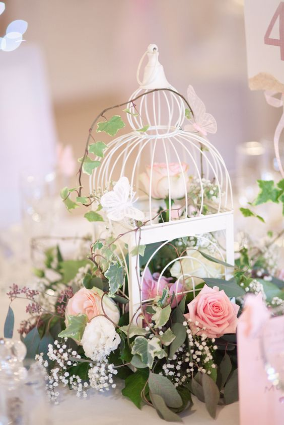 a small white birdcage with lush greenery and white and pink blooms