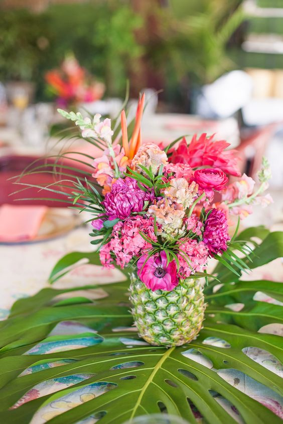 a tropical wedding centerpiece of a pineapple with bold pink blooms displayed on a tropical leaf