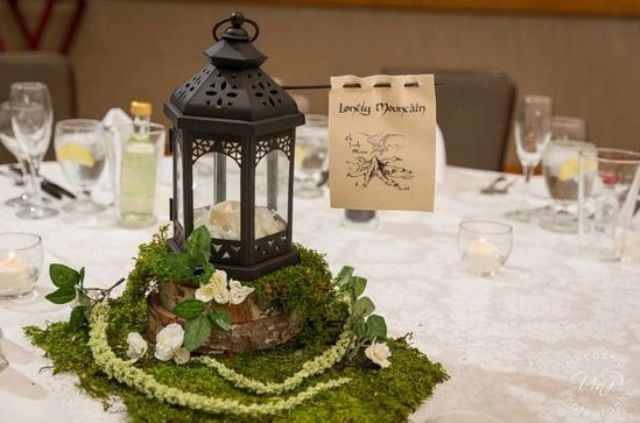 a wedding centerpiece of moss, neutral blooms, a candle lantern and the name of the table