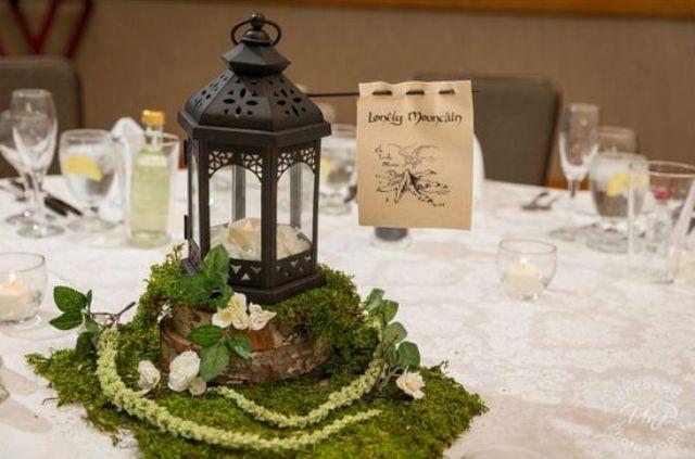 eine Hochzeit Herzstück von Moos, neutralen Blüten, eine Kerze Laterne, und der name der Tabelle