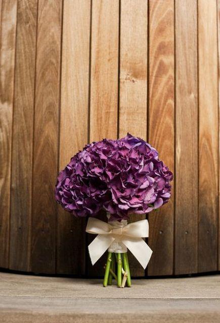 an elegant purple hydrangea wedding bouquet with a white ribbon bow