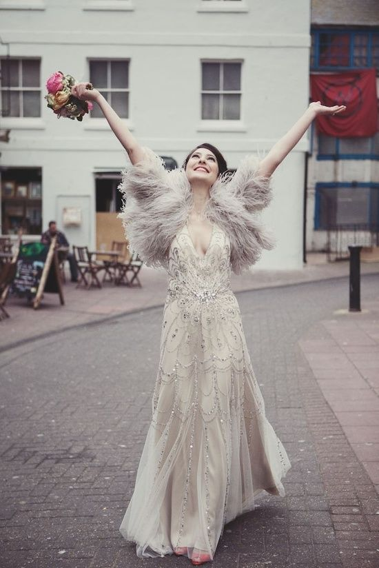 a beaded wedding dress with a deep V-neckline, a faux fur coverup