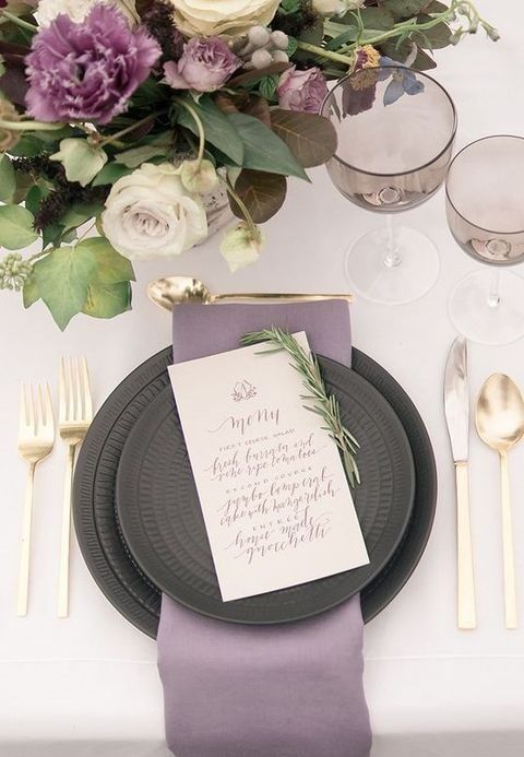 a lavender napkin echoes with the blooms in the arrangement and dark grey plates contrast them