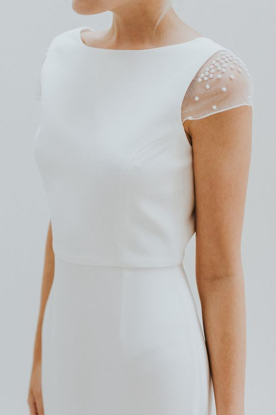 a modern wedding dress with a high neckline and sheer cap sleeves with pearls