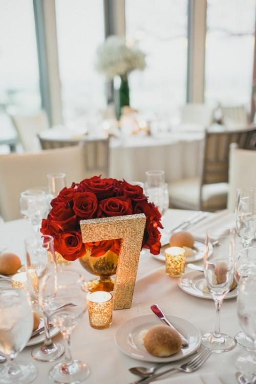 eine rote Rosen canterpiece und ein Glitzer-Tabelle Anzahl und Kerzenhalter sind eine zeitlose Idee