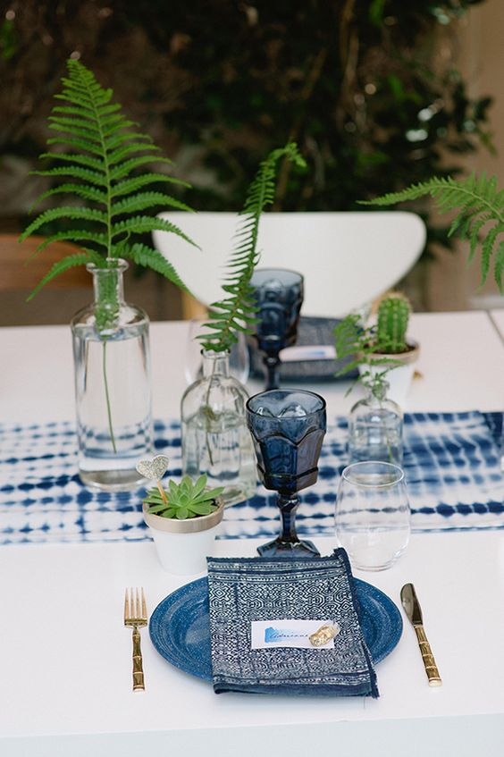a shibori indigo table runner, glasses, printed napkins and plates for a boho forest wedding