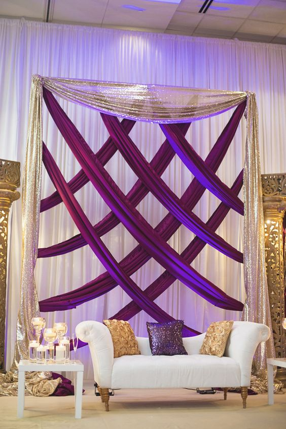 a sparkly wedding lounge with purple and gold glitter draperies, a cream loveseat and pillows in both main colors