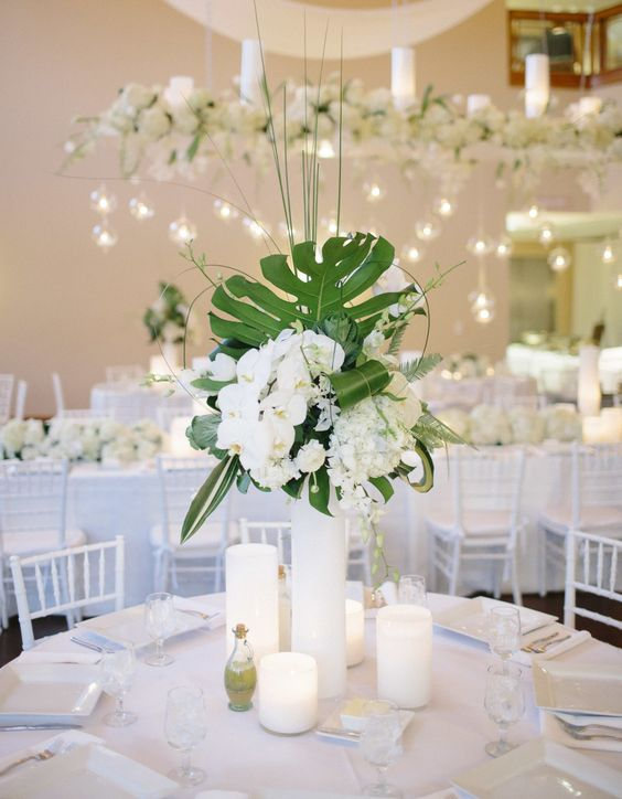 a wedding centerpiece with palm leaves, white blooms and lush orchids