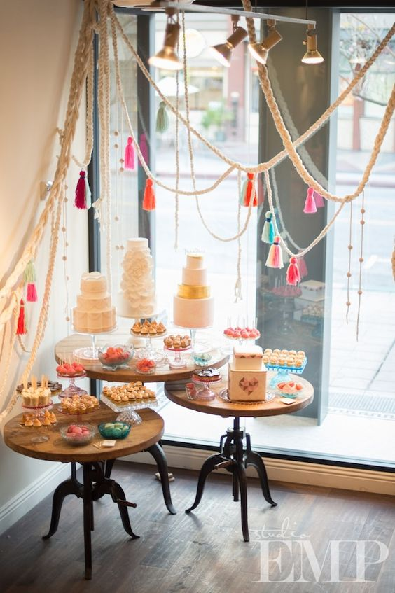 the assortment of wedding cakes and desserts are accentuated with ropes with colorful tassels