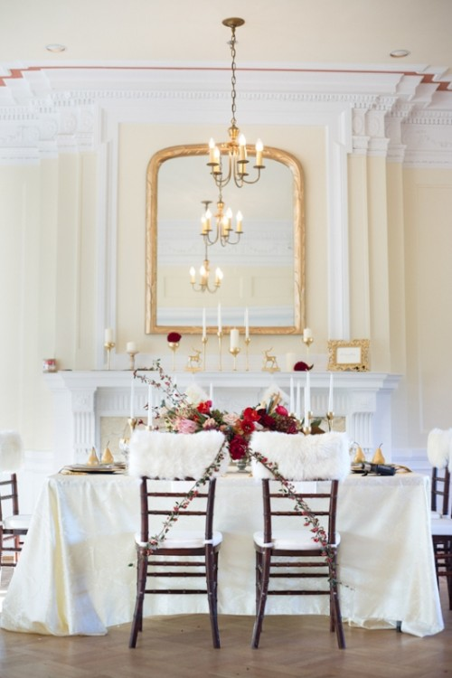 a refined wedding reception space with touches of red and gold and faux fur