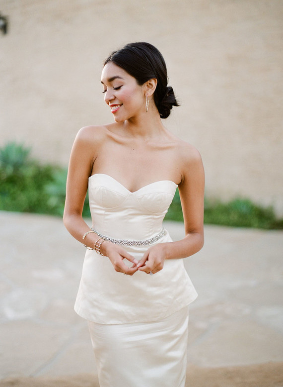 a short fitted peplum wedding dress with an embellished belt and modern jewelry