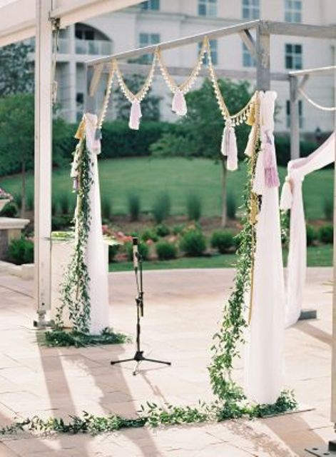 a wedding arch with flowing draperies, greenery, pompom trim and tassels
