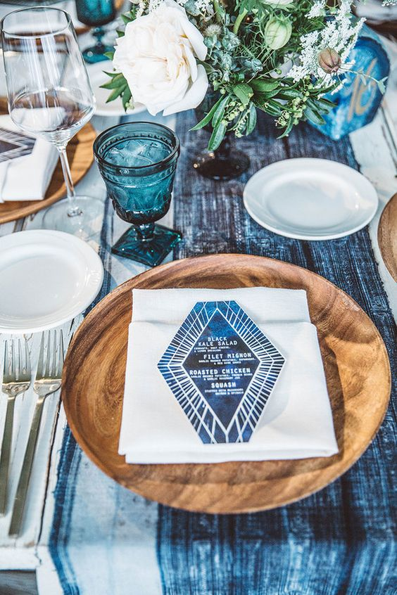 a wedding tablescape with an indigo dyed table runner, indigo glasses and a menu