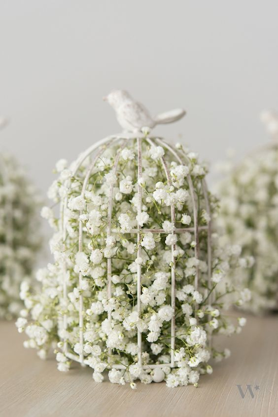 a white cage with a bird on top filled with baby's breath is a simple and cute idea for any wedding