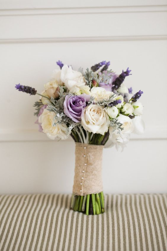 a pale wedding bouquet in cream, grey, lavender colors for a cool look