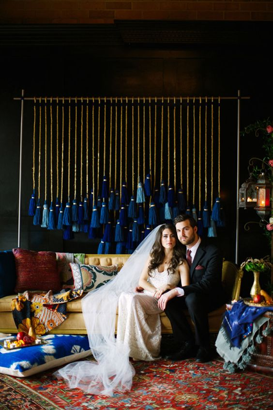 a wedding backdrop with large tassels in the shades of blue for a wedding reception