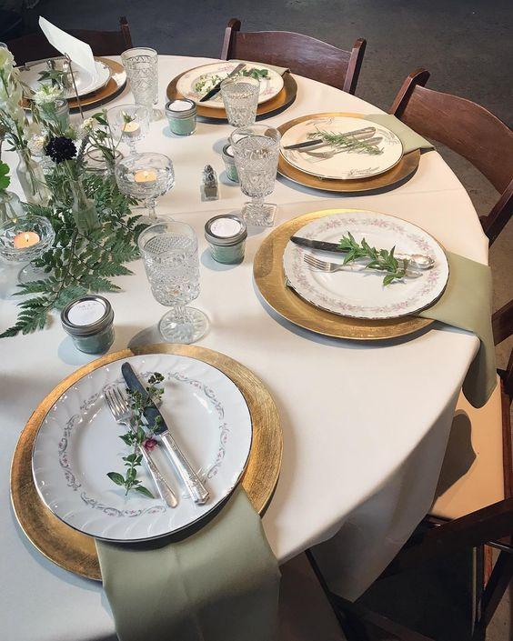 chic Elb-inspirierten Tisch mit gold Ladegeräte, grün, laub und Kerzen