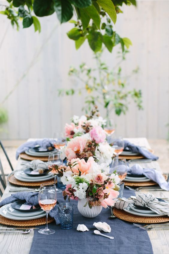 a wedidng tablescape with an indigo table runner, glasses and napkins and pink florals