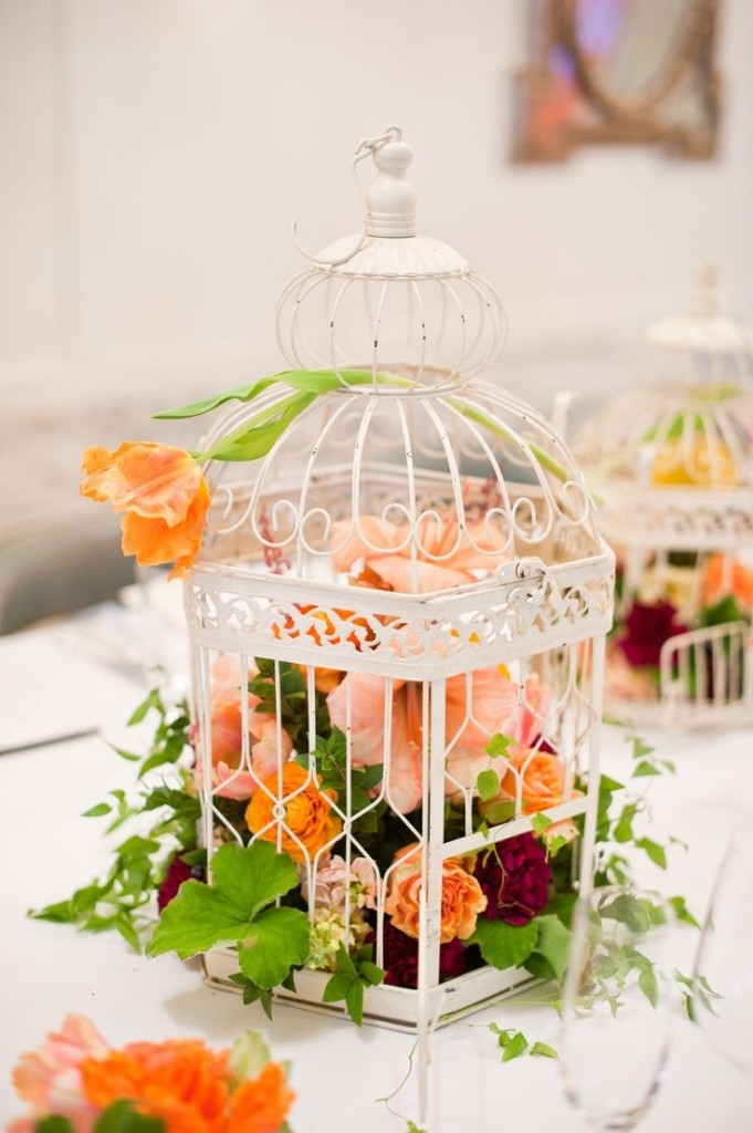 a white cage with lush orange, peachy and burgundy blooms for a bold wedding