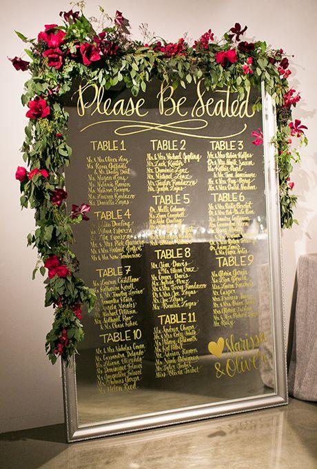 eine überdimensionale Spiegel Sitzplan mit gold Kalligraphie, roten Rosen und viel grün